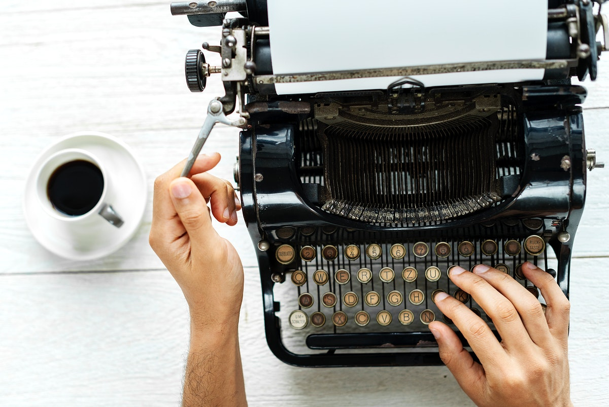 Aerial view of a man typing on a retro typewriter blank paper