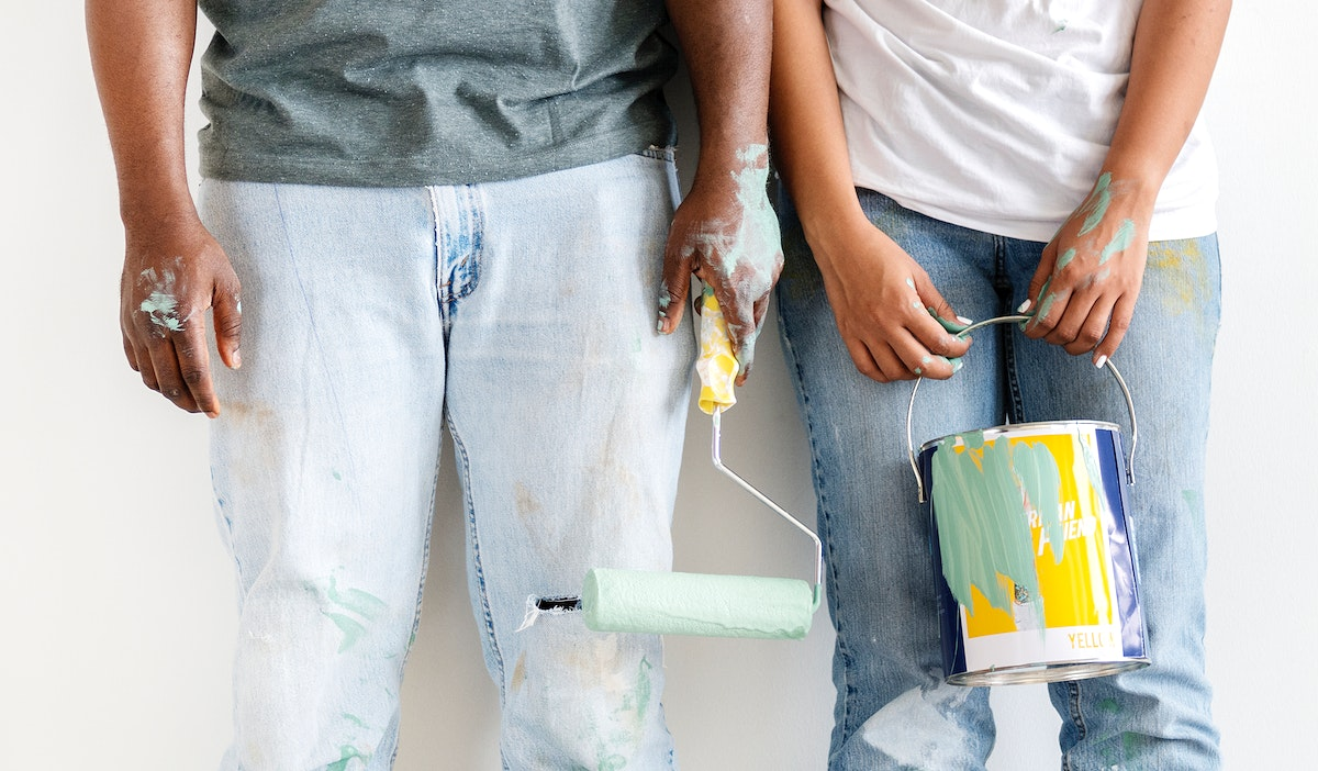 Happy couple painting house wall for interior design