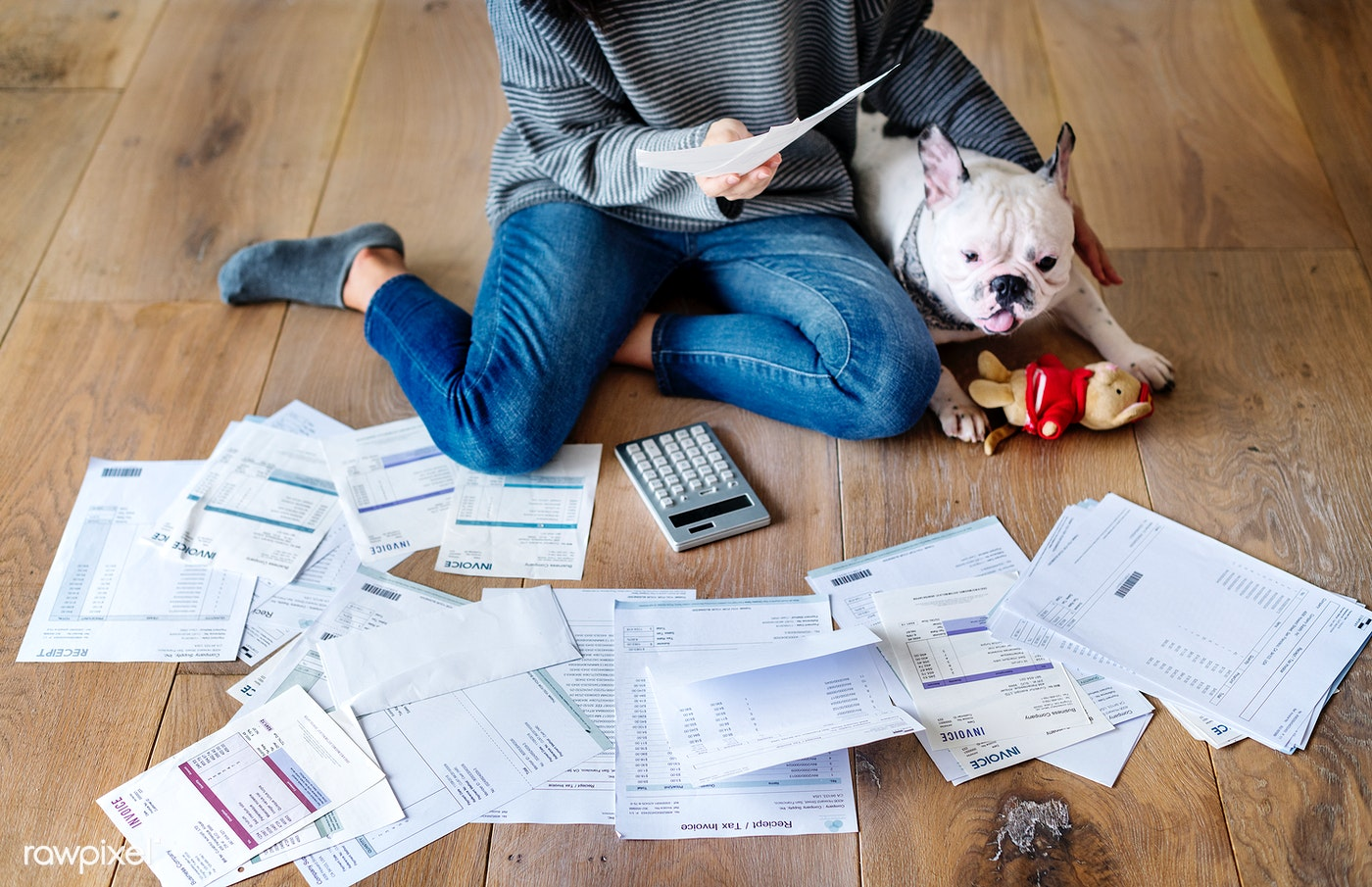 Sorting out a pile of bills on the floor