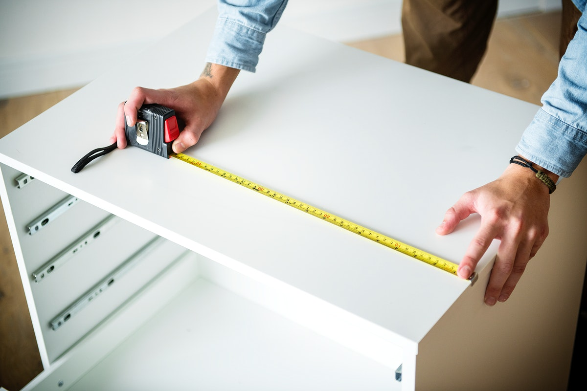 Man measuring the cabinet with measurement tape