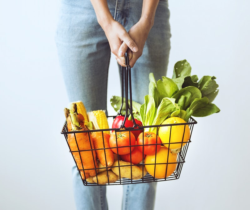 A woman holding a grocery basket with fruits and vegetables inside them