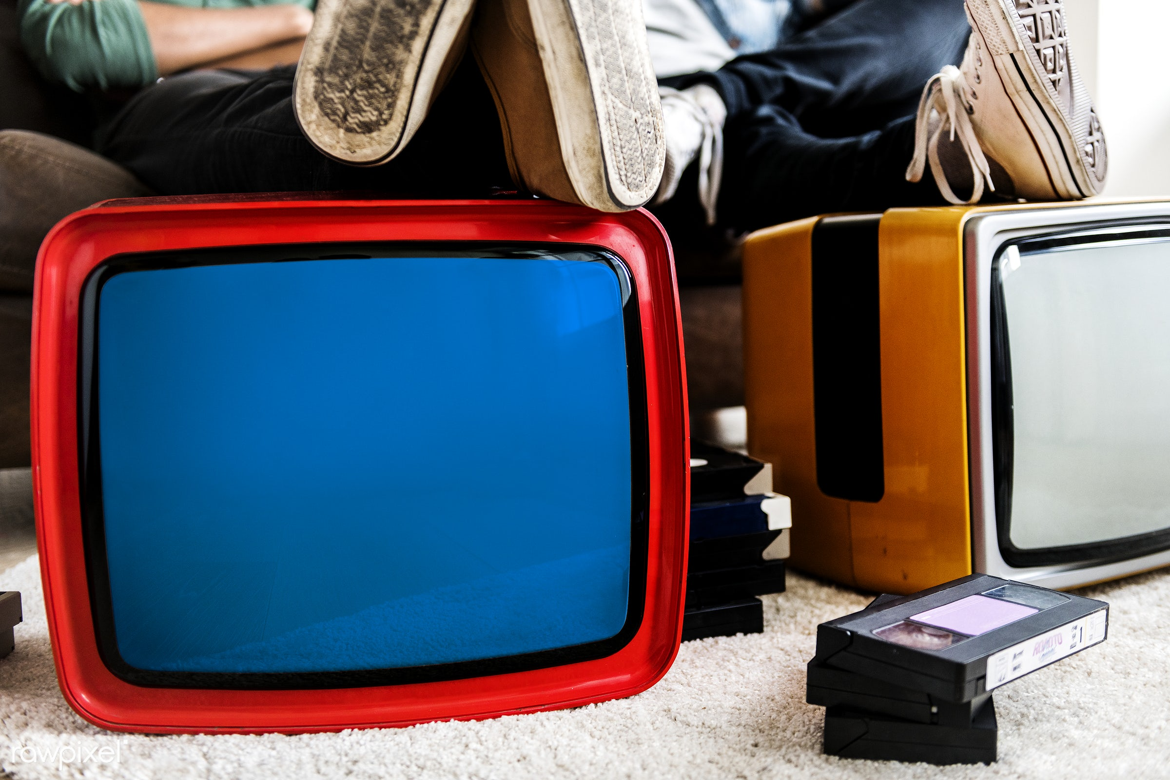 two man sitting next to retro televisions