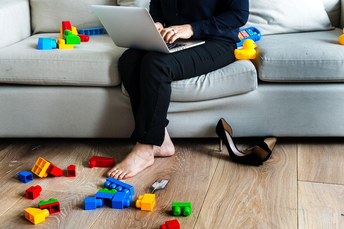 Woman working on laptop on sofa