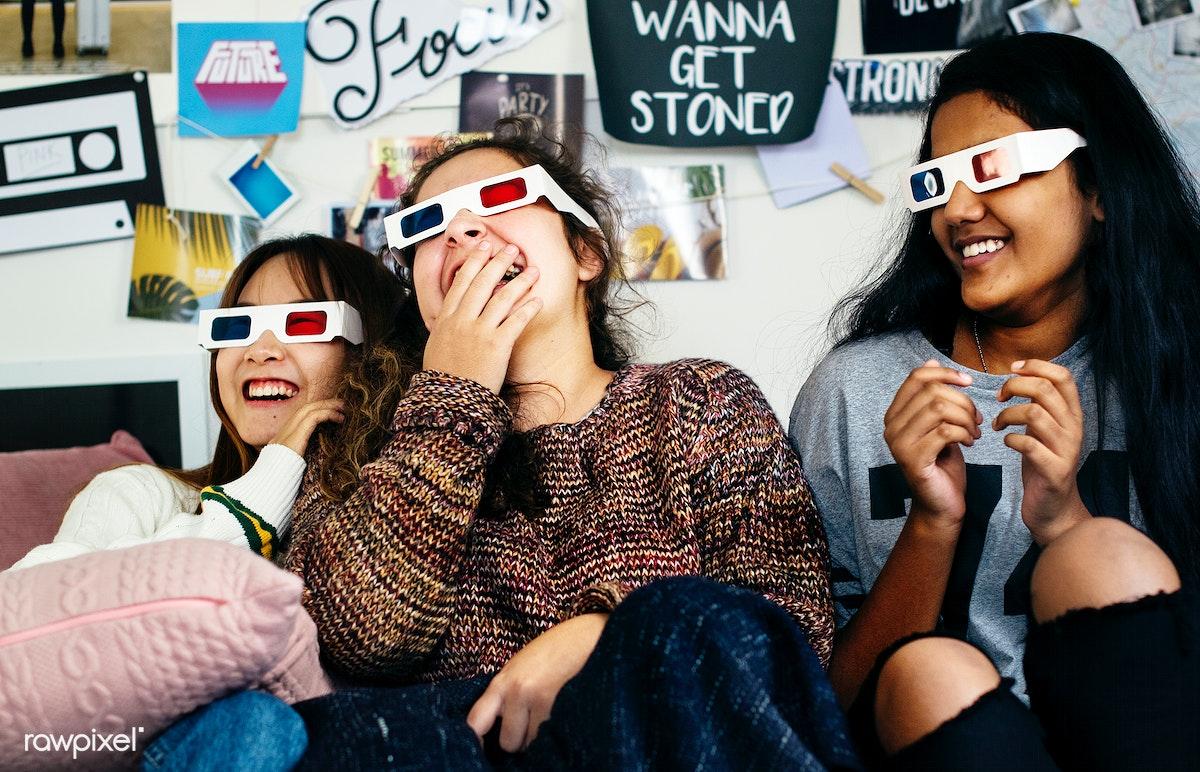 17af1045cc79d Teenage girls wearing 3d movie eyeglasses enjoying laughing and watching TV