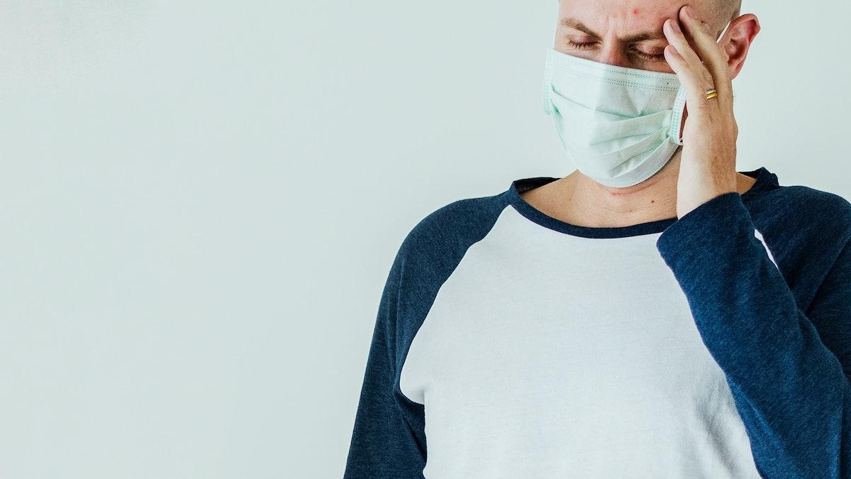 Sick man wearing surgical mask having a headache