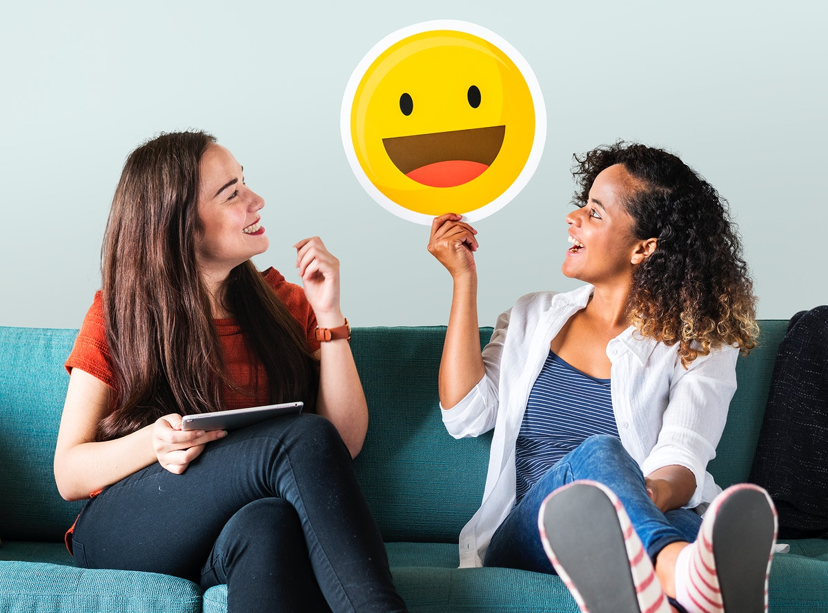 Woman holding emoticons on a couch