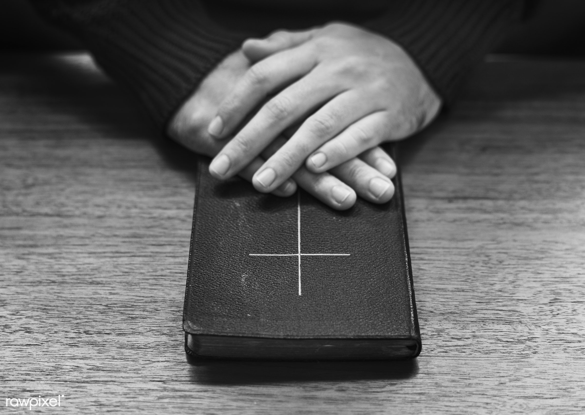 Hands over bible on wooden table - belief, believe, bible, black and white, book, bw, catholic, christian, christianity,...
