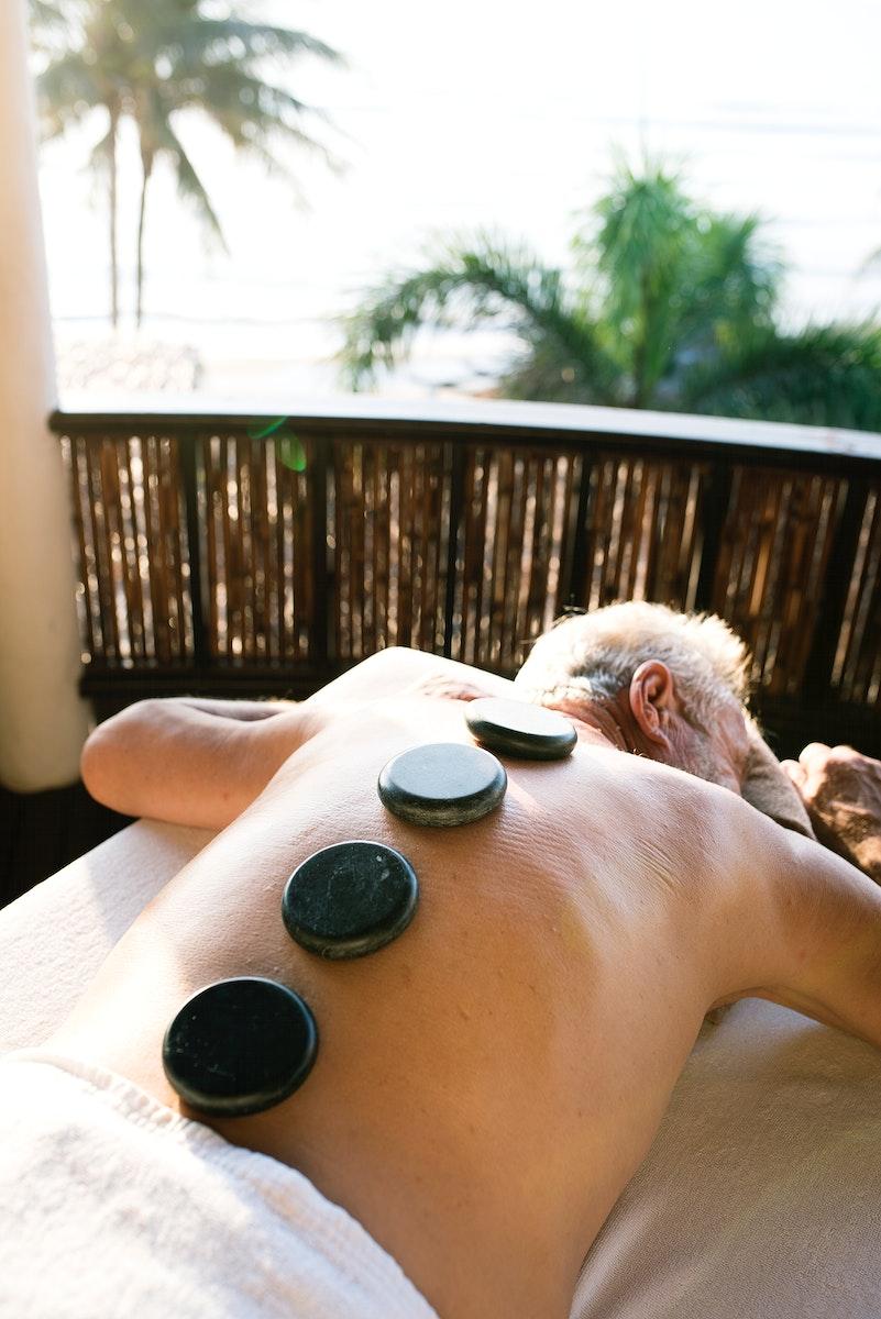 Mature man getting hot stone massage