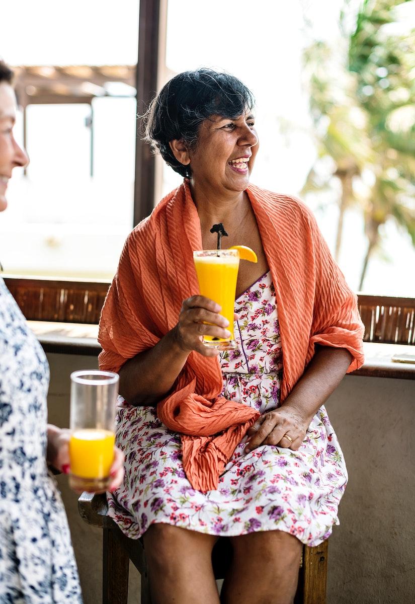 Senior woman drinking orange juice at a resort