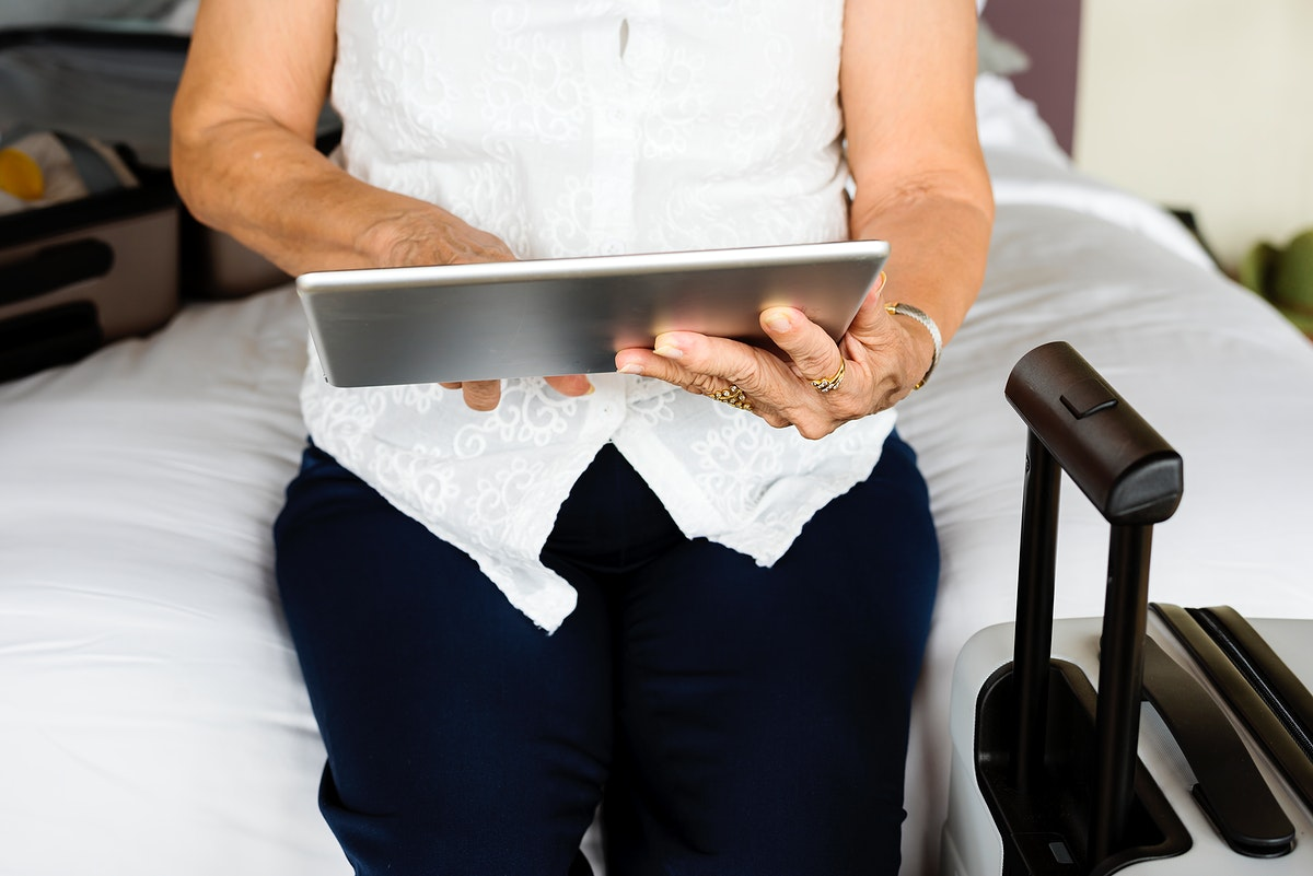 Senior woman using tablet on a bed
