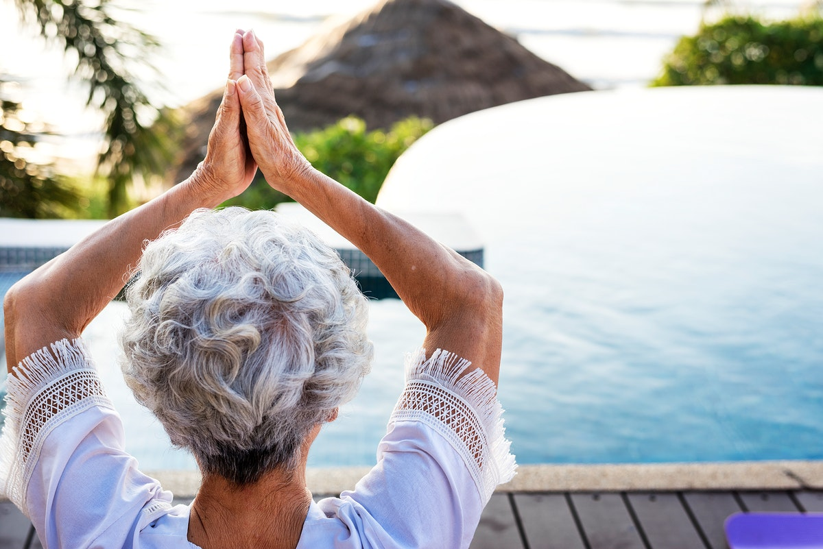 Senior adult practicing yoga by the pool
