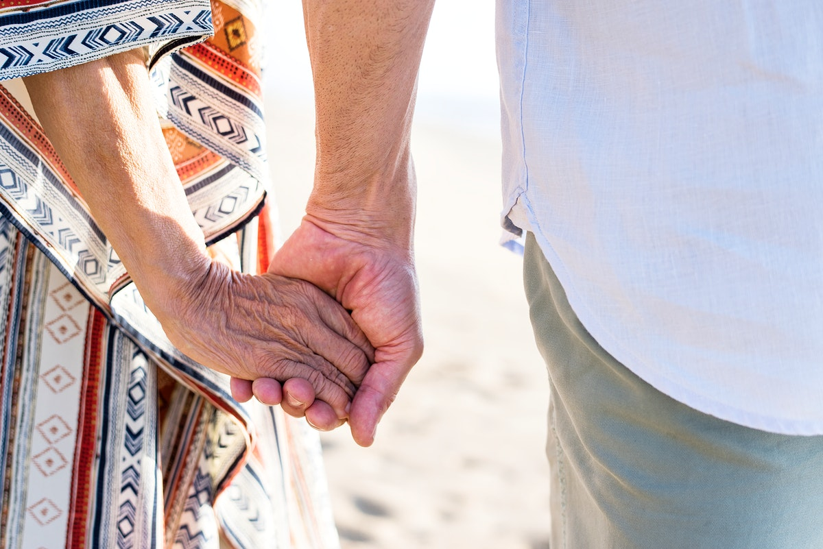 Mature couple holding hands at the beach