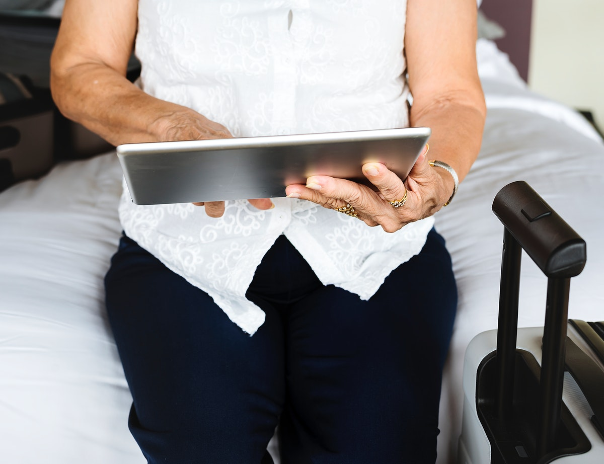 Senior woman using a tablet on the bed