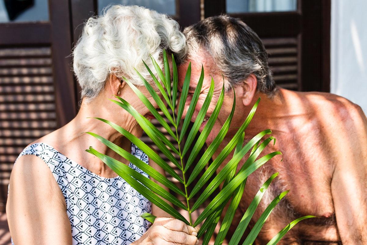 Senior couple cuddling behind a leaf