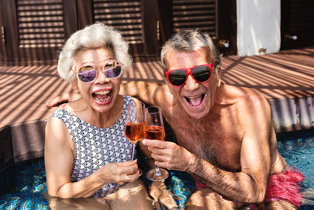 Happy seniors drinking prosecco in the pool