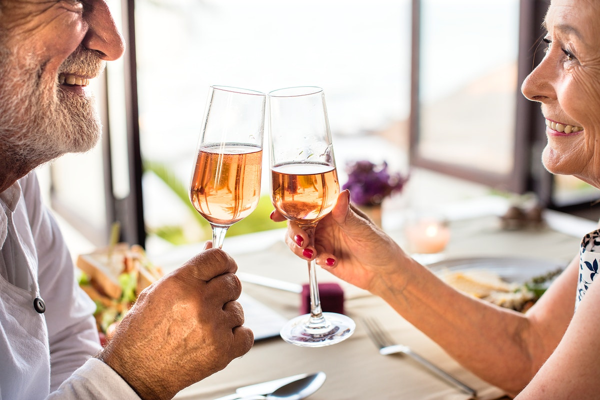 Cheerful senior couple drinking rose champagne