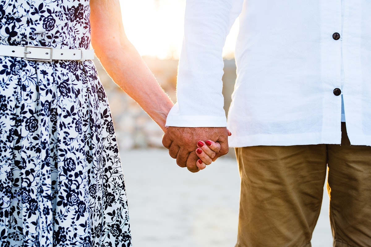 Mature couple holding hands in the sunset