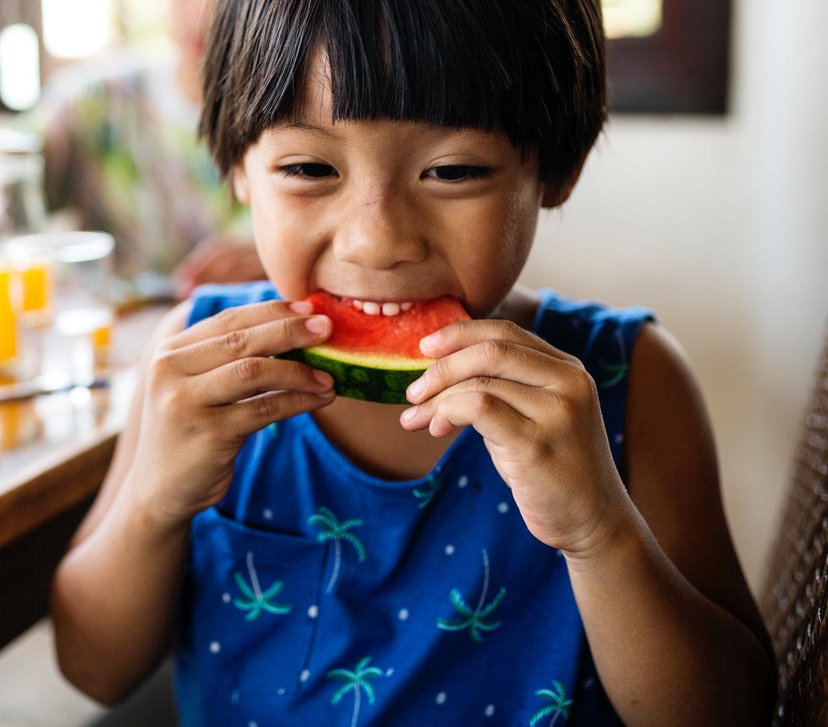 Little boy enjoying a piece of watermelon