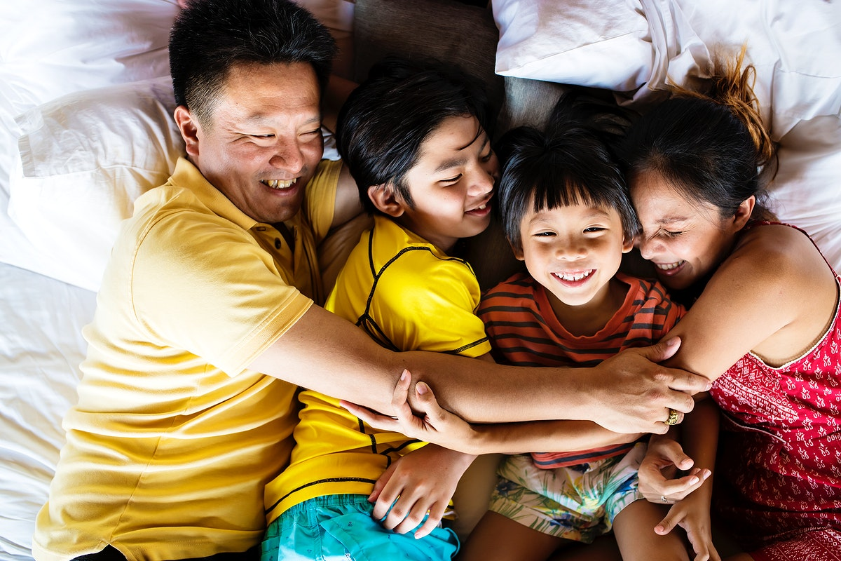 Family hugging together on the bed