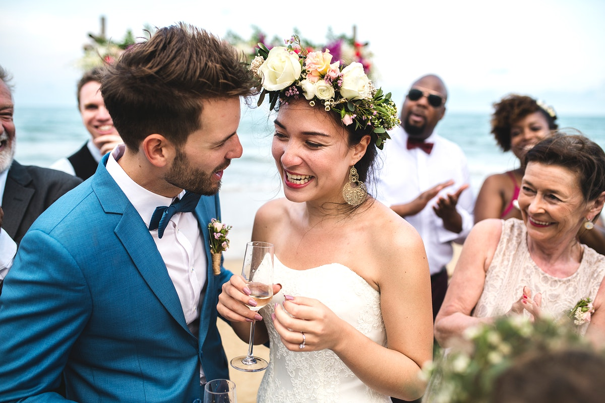 Newly weds with their guests at their beach wedding