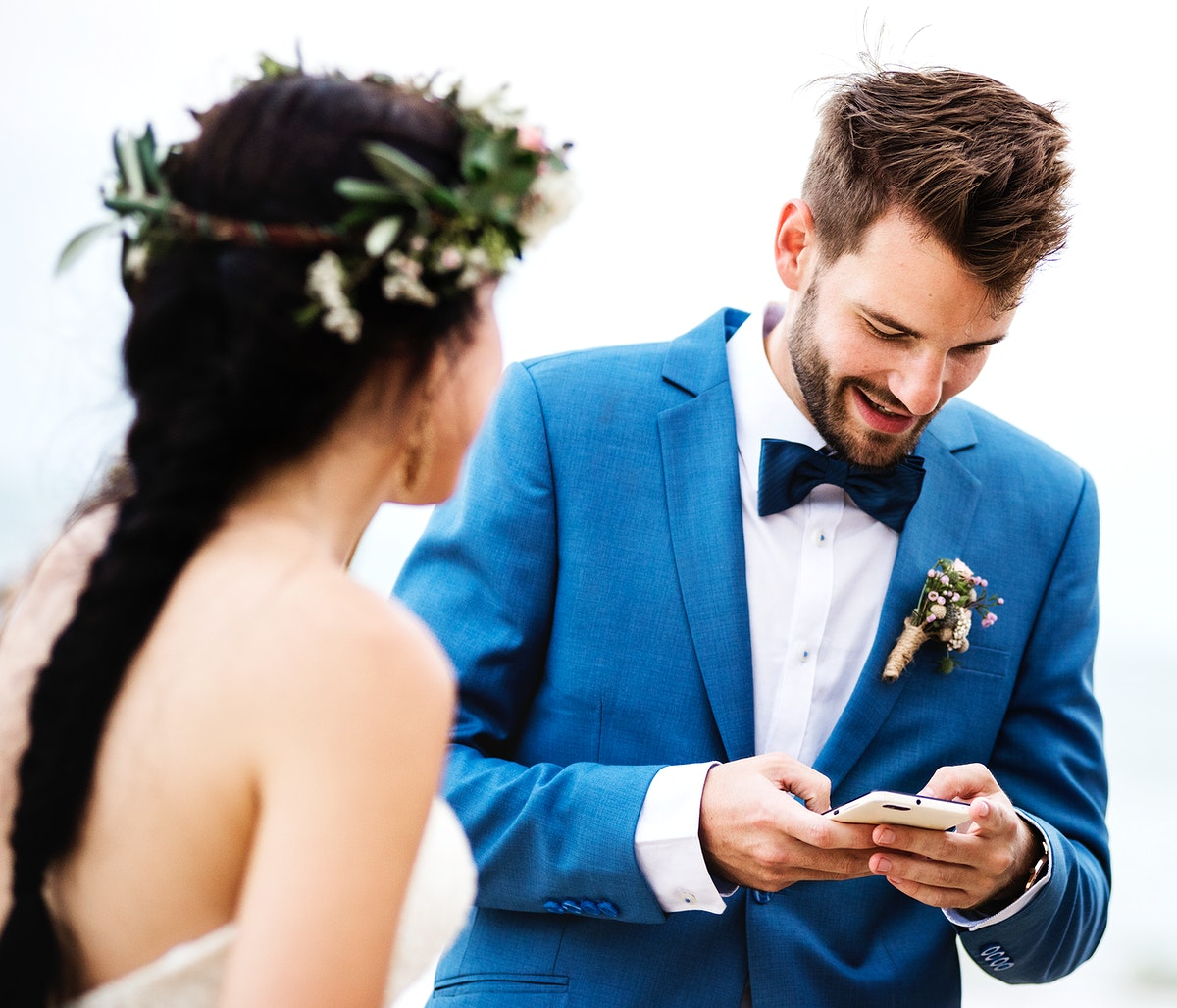 Groom checking his phone at beach wedding ceremony