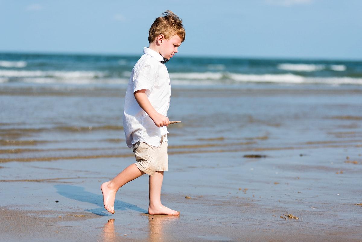Little boy walking at the beach