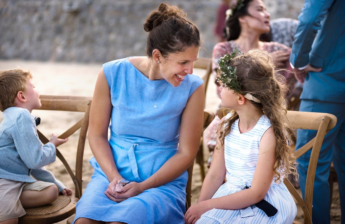 Woman talking to young girl at a beach wedding