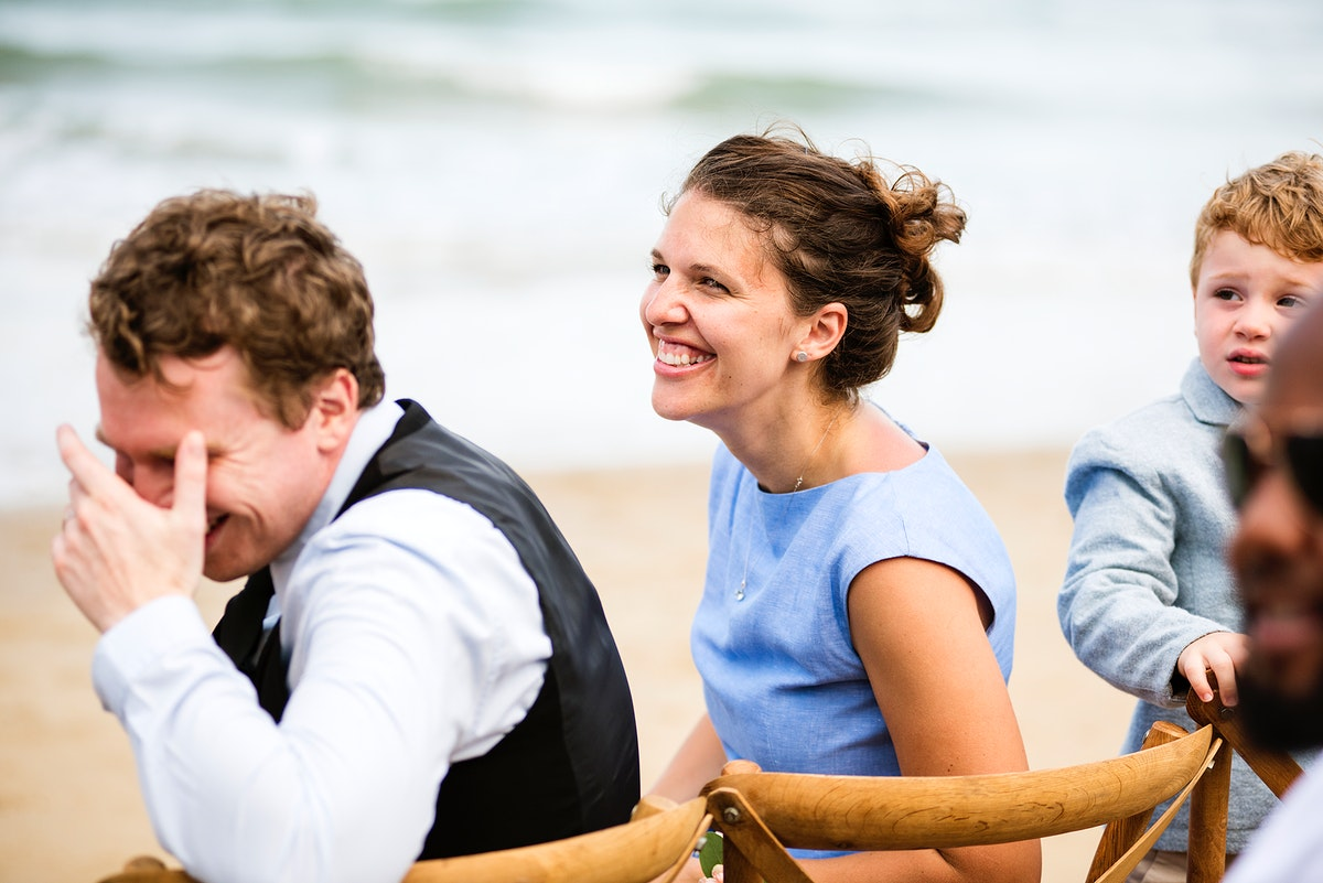 People laughing at a beach wedding