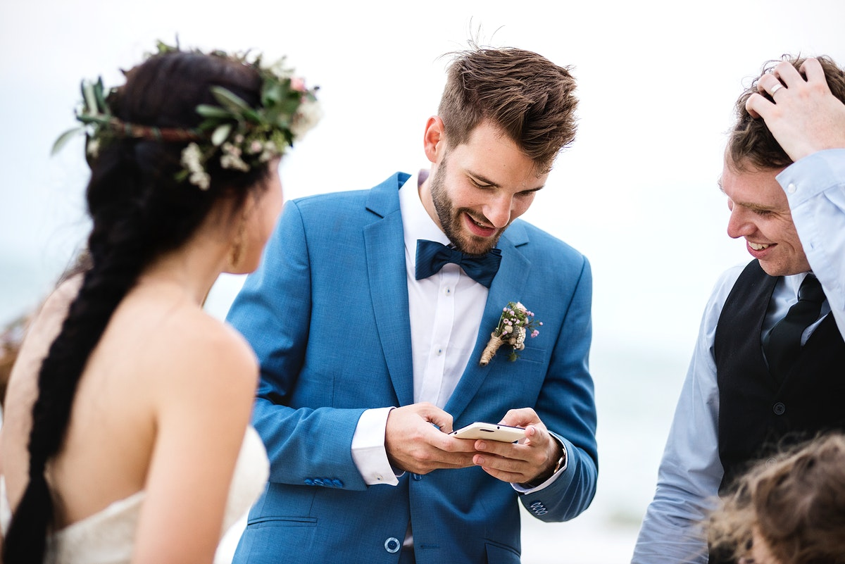 Groom occupied with phone at beach wedding ceremony