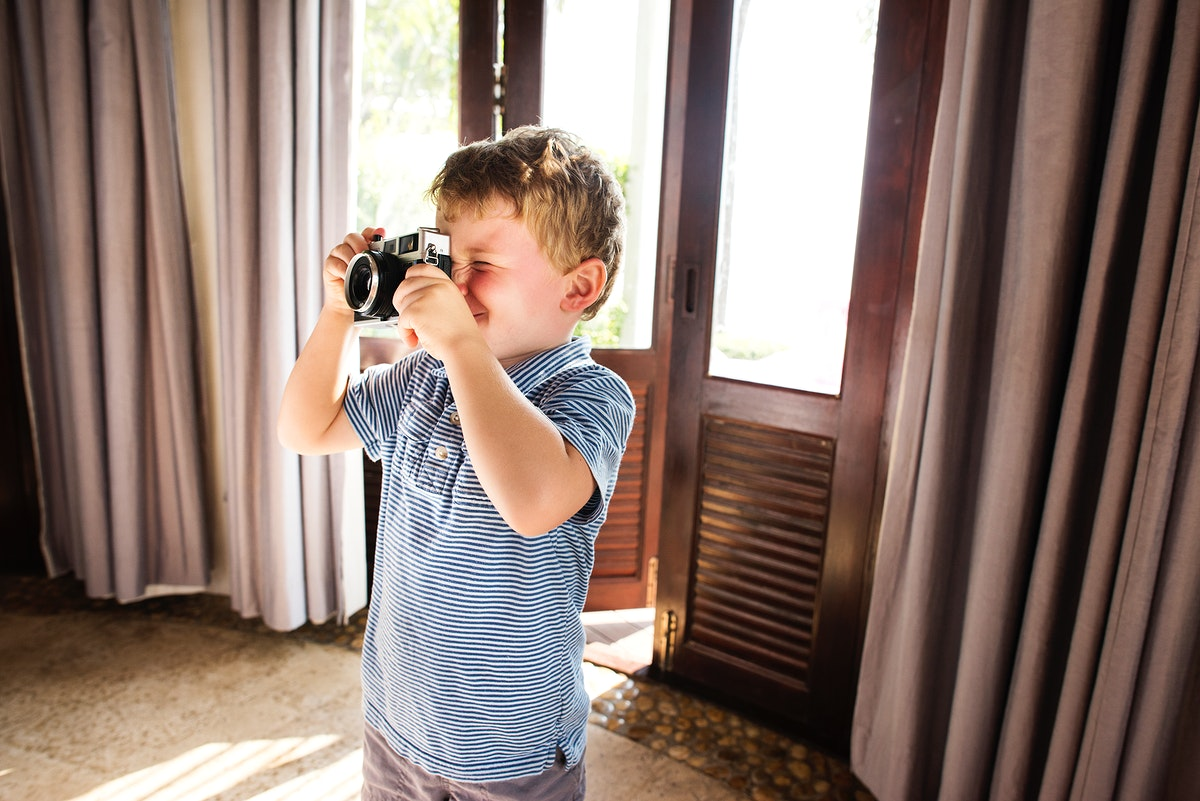 Young boy taking photos with vintage film camera