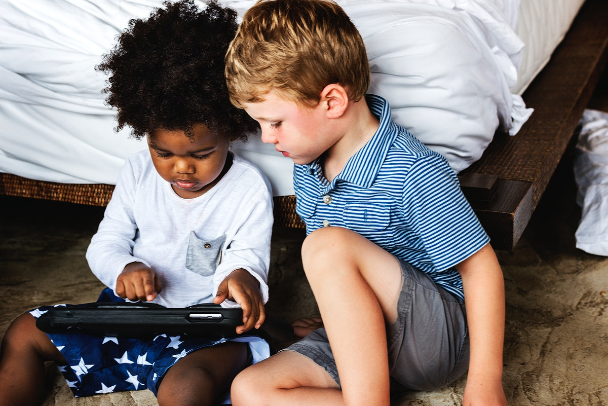 Friends playing with tablet in bedroom