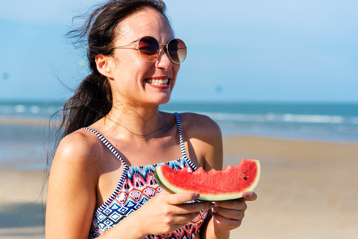Young woman holding watermelon at the beach