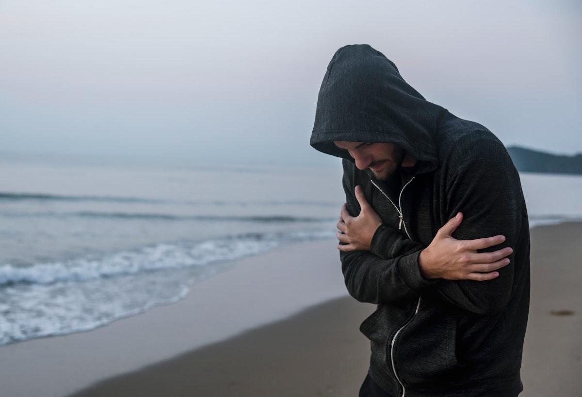 Caucasian man walking alone at the beach