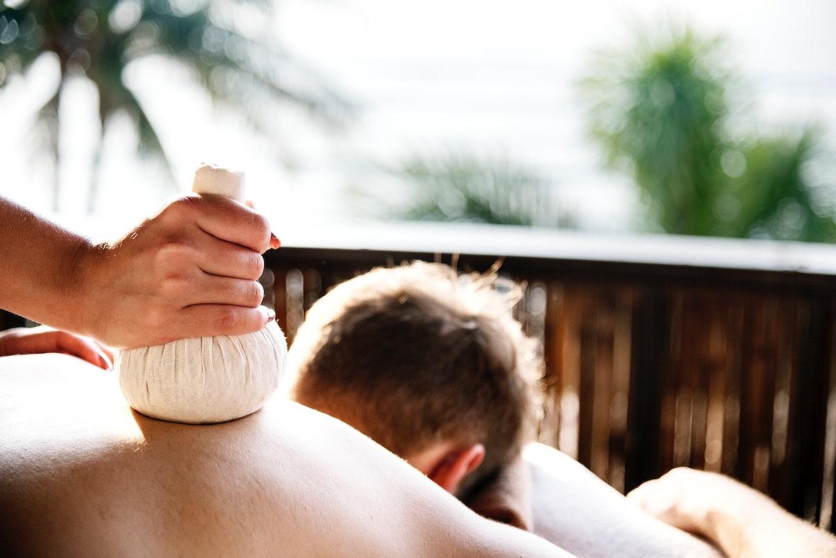Man having an herbal compress massage at a spa