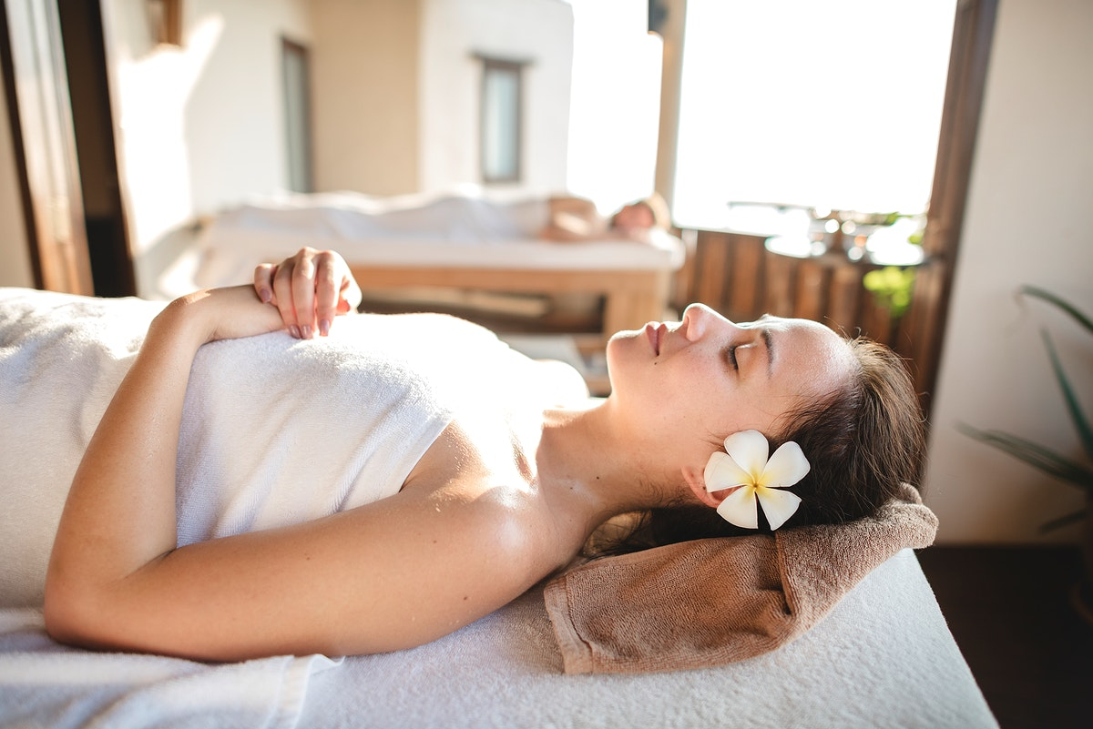 Caucasian woman relaxing with herbal massage