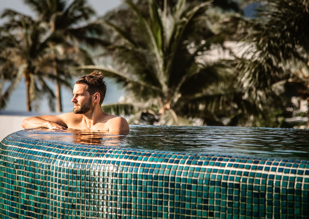 Handsome guy relaxing in swimming pool