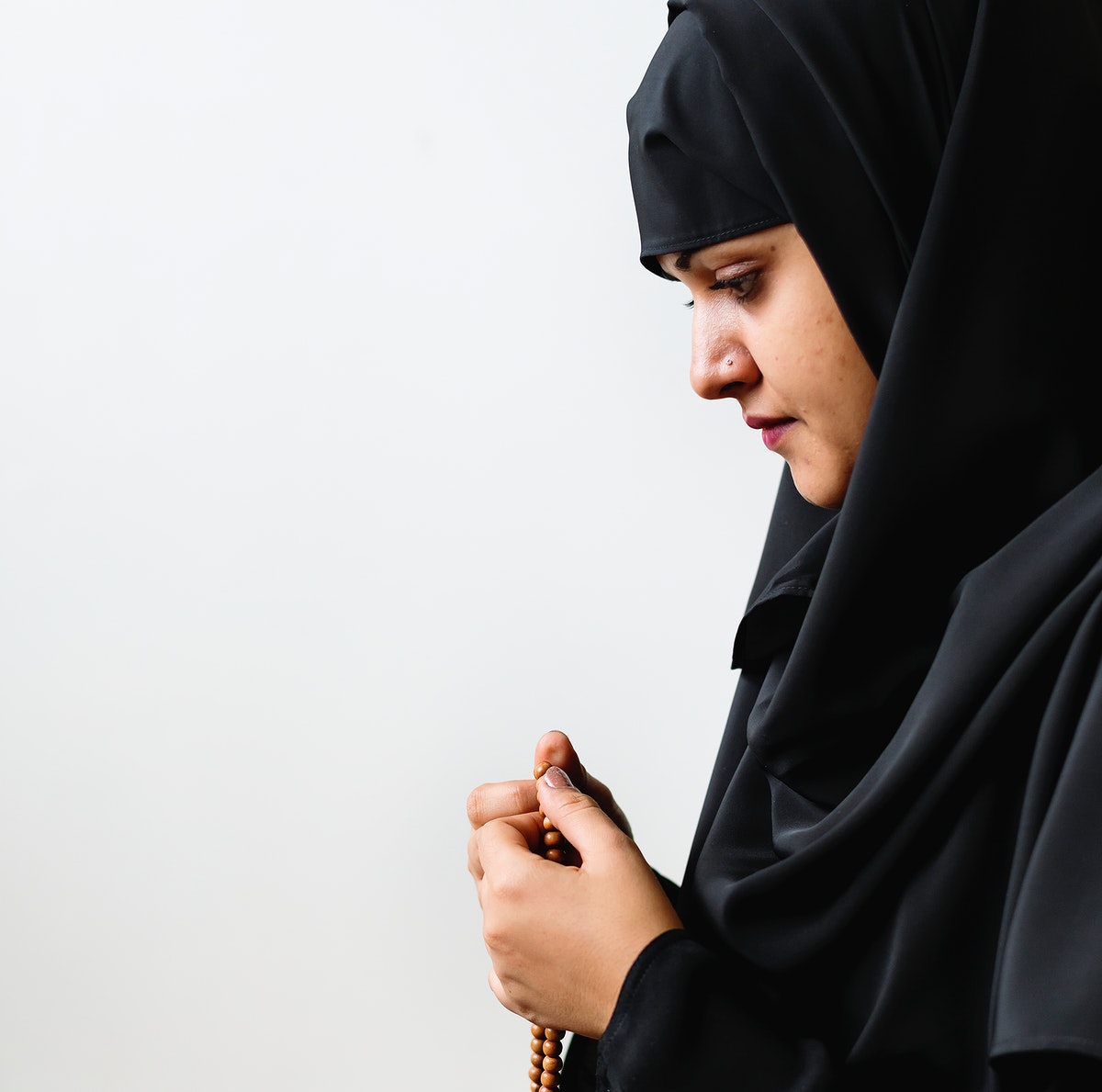 Muslim woman using misbaha to keep track of counting in tasbih