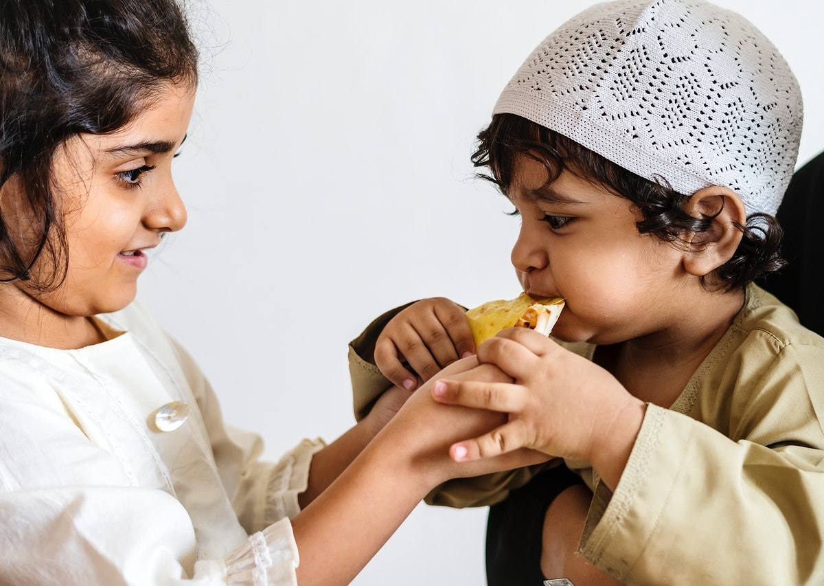 Sister sharing pita bread with her brother
