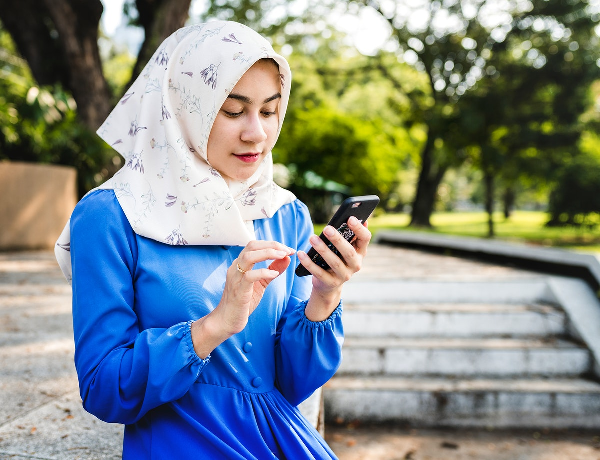 Muslim woman using a smartphone in the park