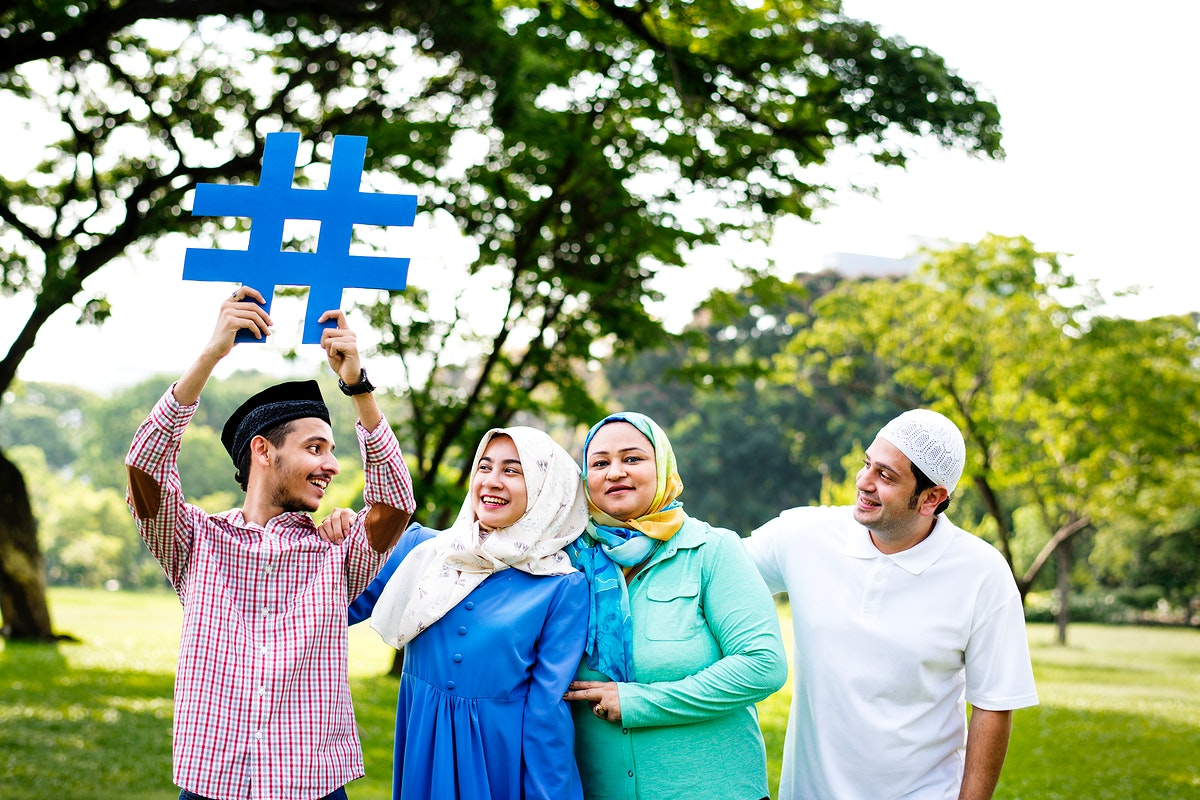 Muslim family holding up a hashtag