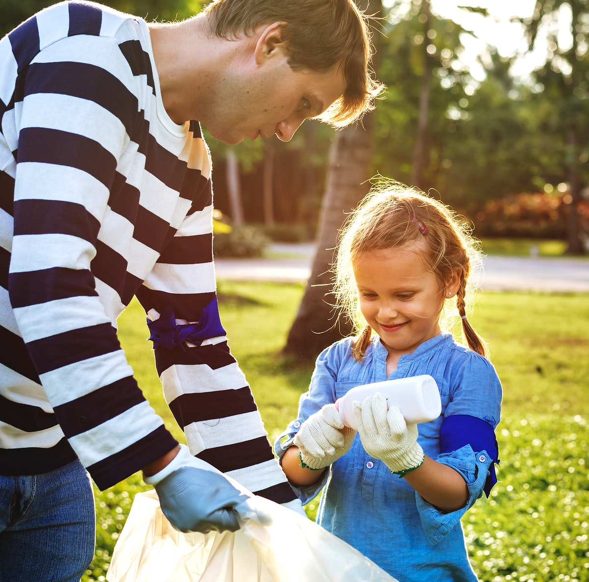Father and daughter cleaning the park