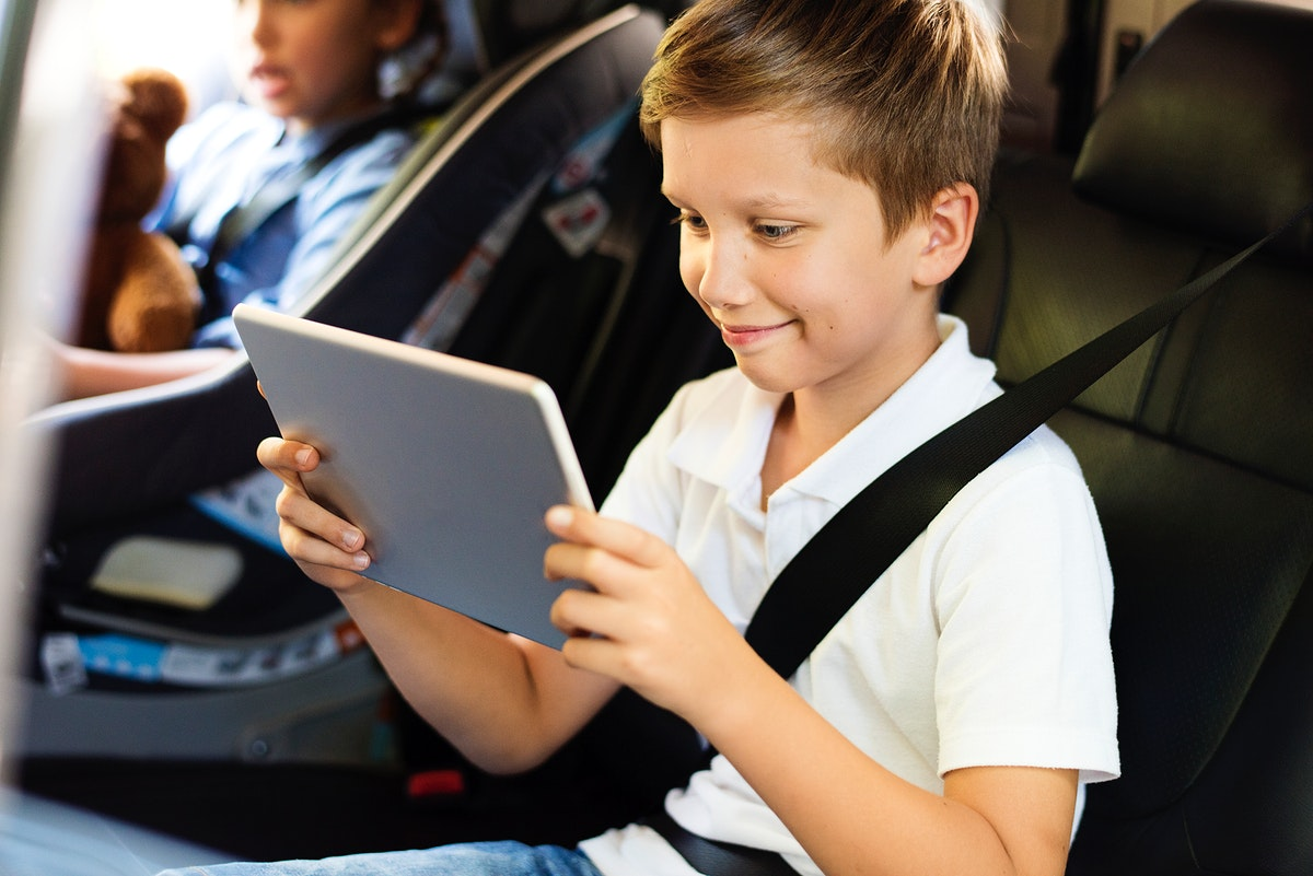Boy playing on a digital tablet in the car