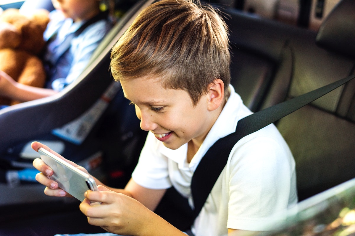 Boy playing on a smartphone in the car