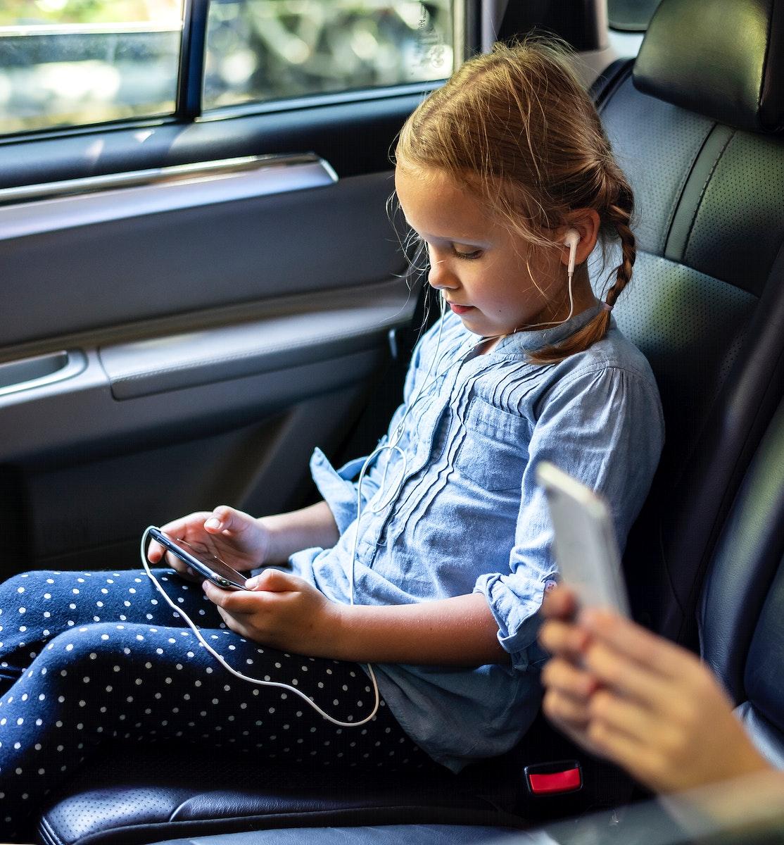 Girl in a car using a digital device