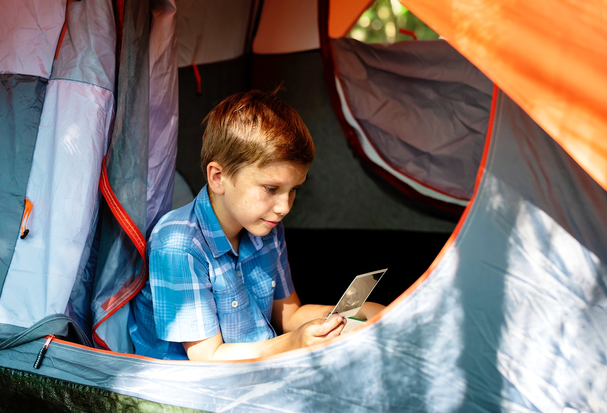 Little boy camping in the forest