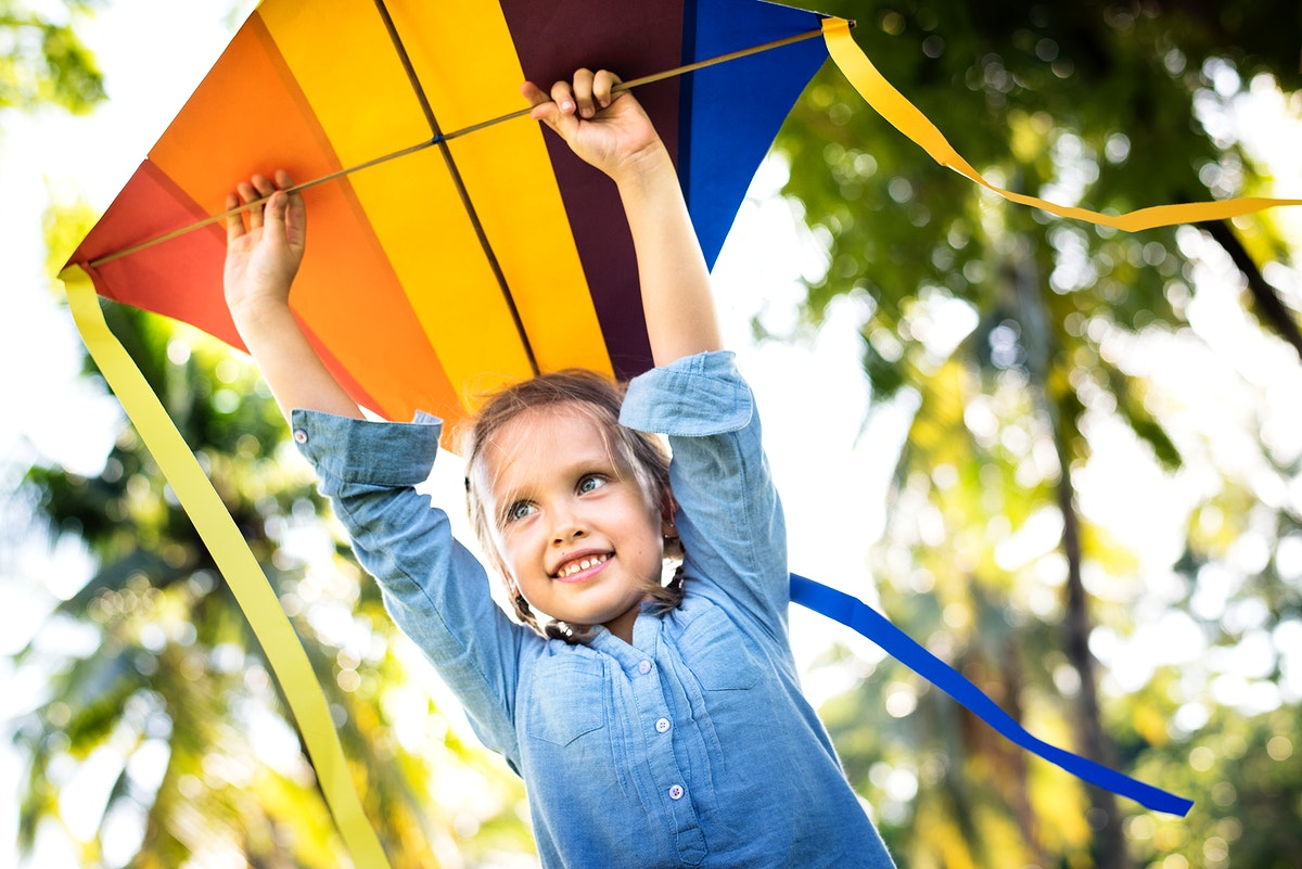 Girl playing with a colorful kite
