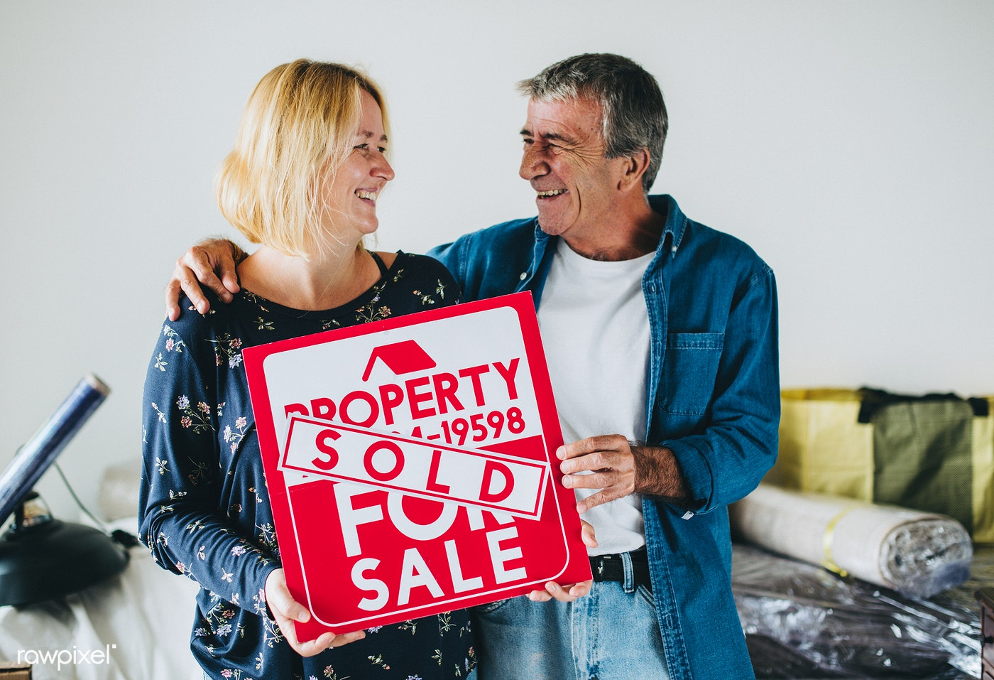Couple with a property for sale sign