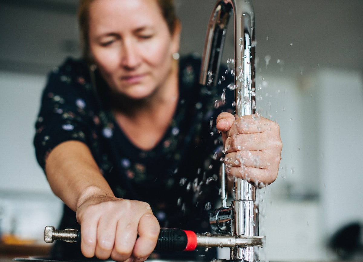 Handy woman fixing the faucet