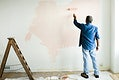 Man painting the walls pink