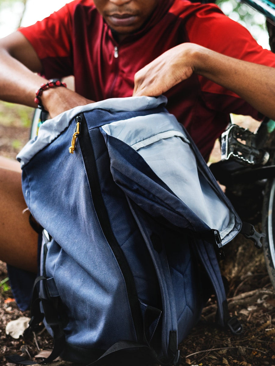 Cyclist getting stuff from backpack